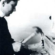 George Maciunas performing 'Carpenter's Piano Piece', 1964